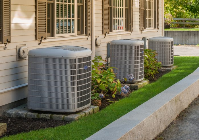 Three air conditioners outside of a home